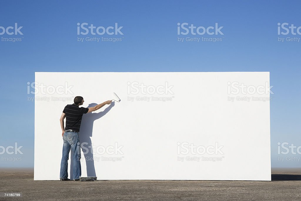 Man painting wall outdoors stock photo