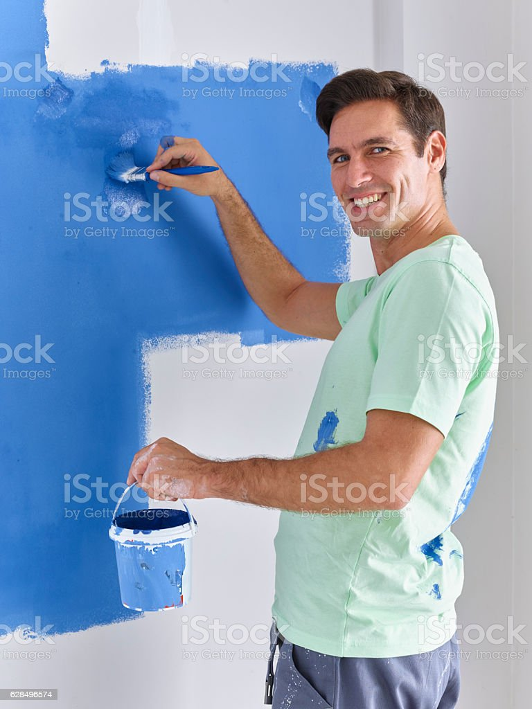 Man painting wall with a brush stock photo