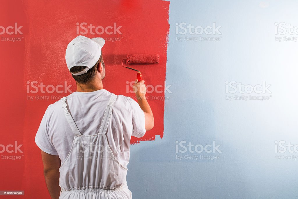 Man painting wall with roller stock photo