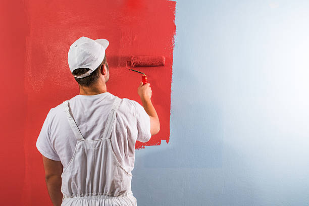 man painting wall with roller - painter stock photos and pictures