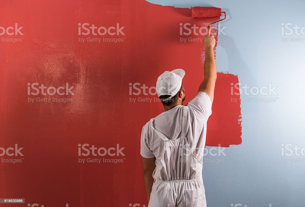 Mann Malerei Mauer mit Rollschnalle Lizenzfreies stock-foto