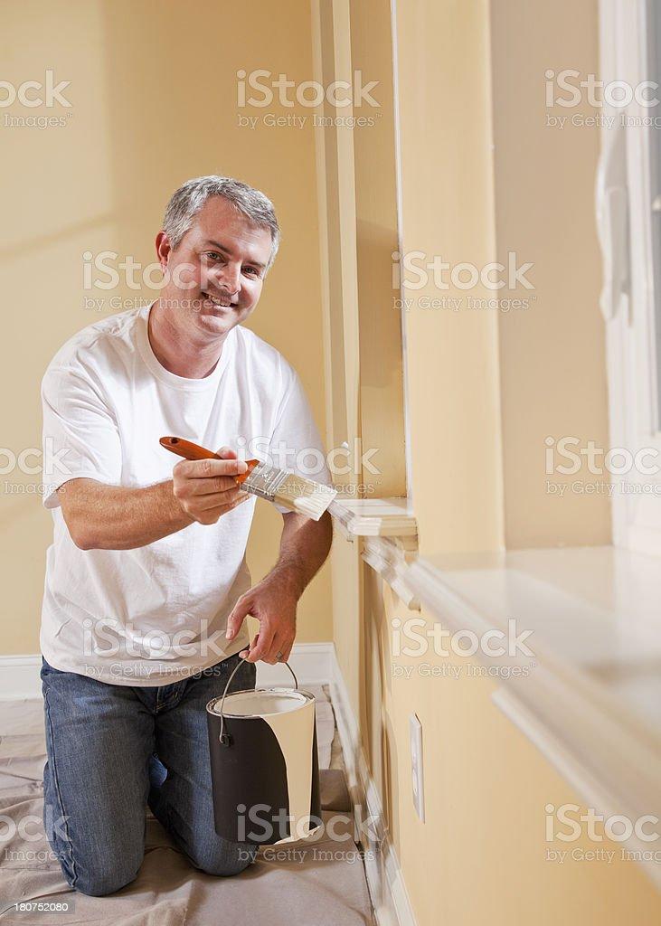 Man painting window sill stock photo