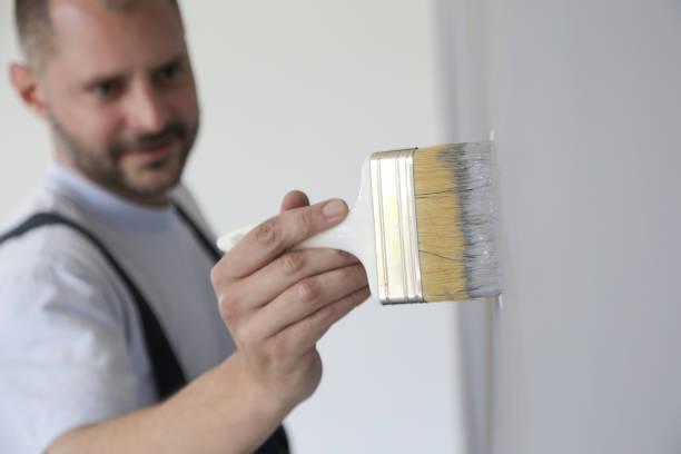 Mann malt mit einem Pinsel über eine graue Wand – Foto