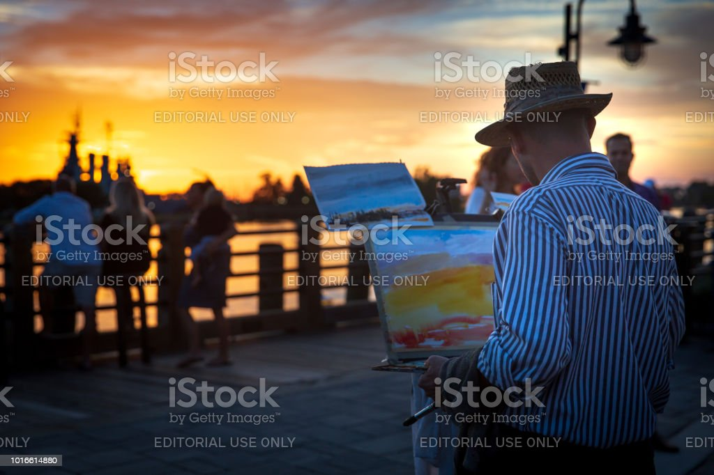 A man paints a picture of the sunset along the Cape Fear River stock photo