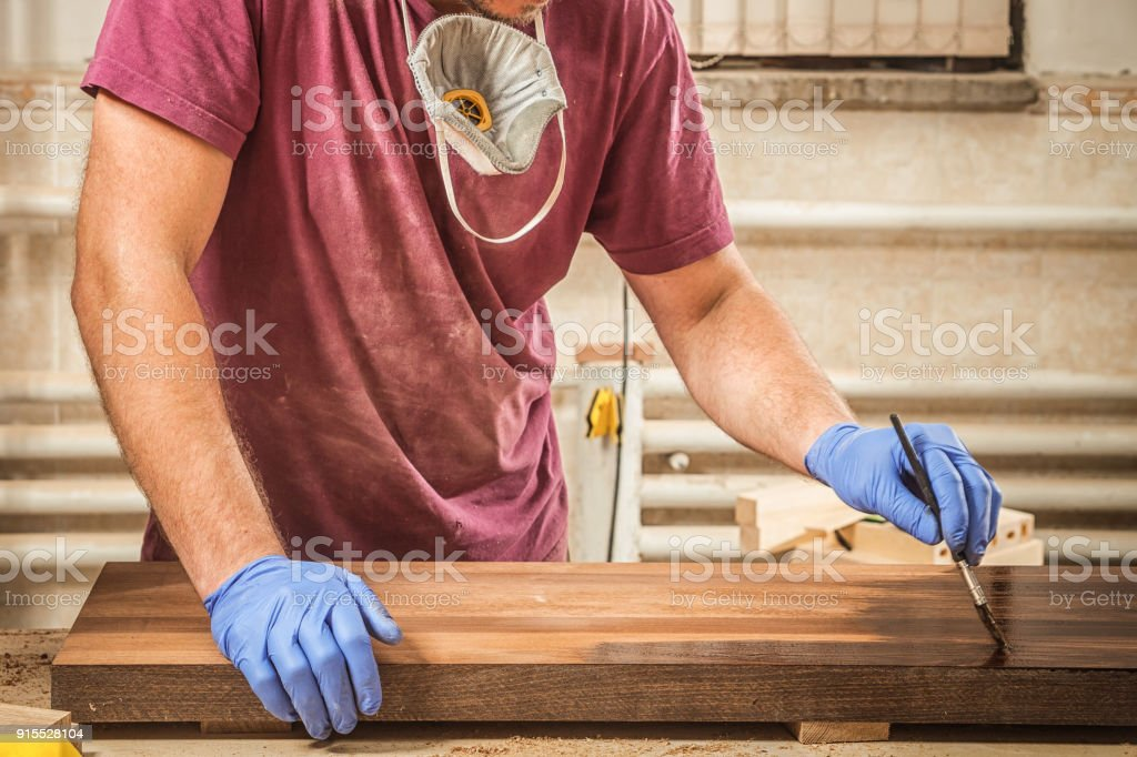man paints a wooden stock photo
