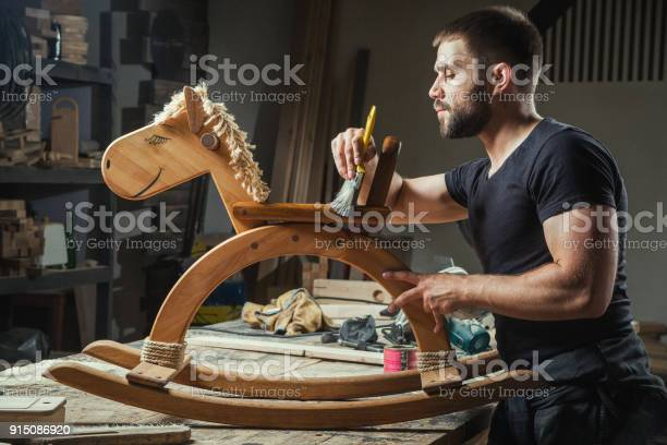 Man paints a wooden toy picture id915086920?b=1&k=6&m=915086920&s=612x612&h=evzw7yv67h6xudtoqkmrjods57duyp4t89f9debzew0=