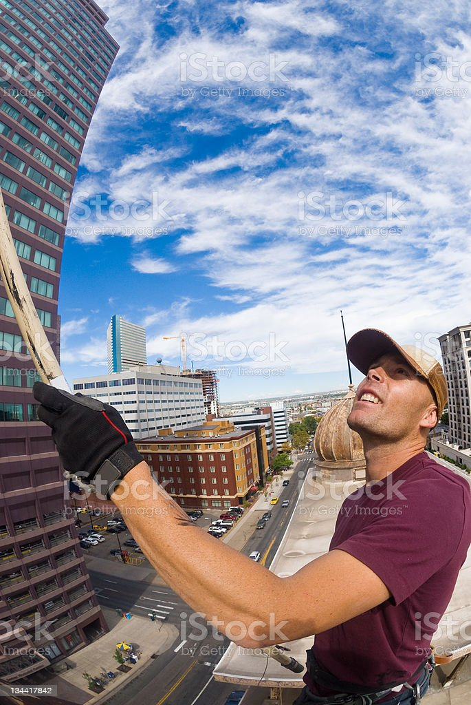 Man Paints Flagpole on Downtown Skyscraper Denver royalty-free stock photo