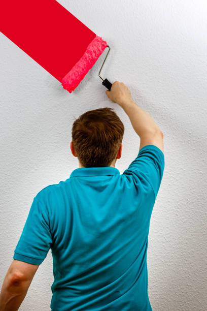 Man paints wall red, close up stock photo