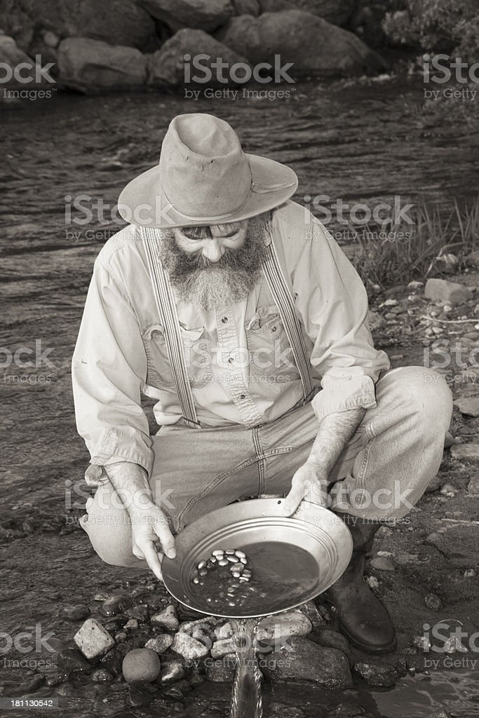 Man Panning For Gold In A Stream stock photo