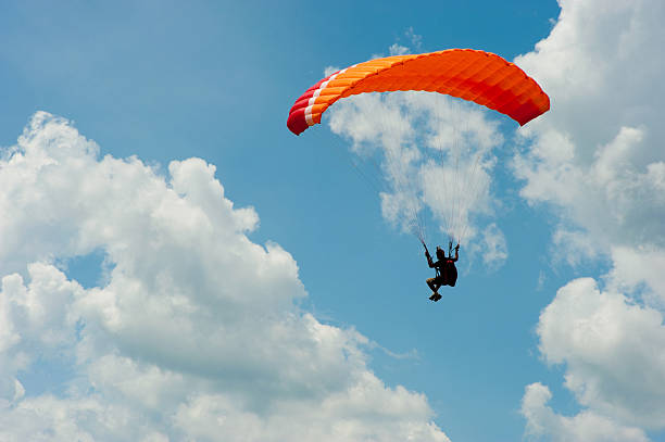 A man paragliding in the blue sky paragliding in blue sky paragliding stock pictures, royalty-free photos & images