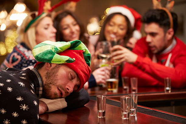 Man Passed Out On Bar During Christmas Drinks With Friends Man Passed Out On Bar During Christmas Drinks With Friends, Wearing Christmas Hats drunk stock pictures, royalty-free photos & images