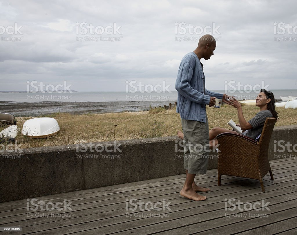 Man passes cup to woman sitting at beach royalty-free stock photo