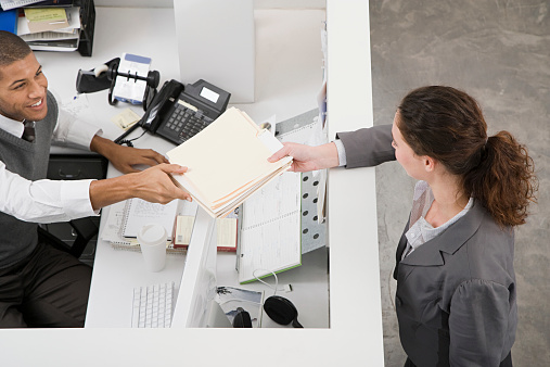 Man passing file to colleague