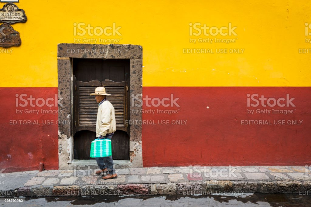 Man passing in front of a door in the historic center of the city of San Miguel de Allende, Mexico. stock photo