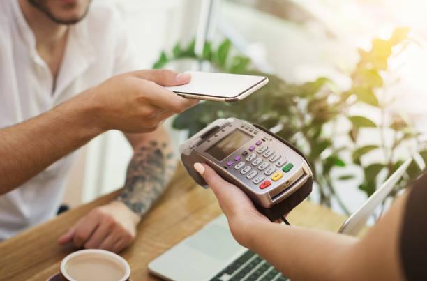 男人付錢給條例草案通過 nfc 技術的智慧手機 - 車站 個照片及圖片檔