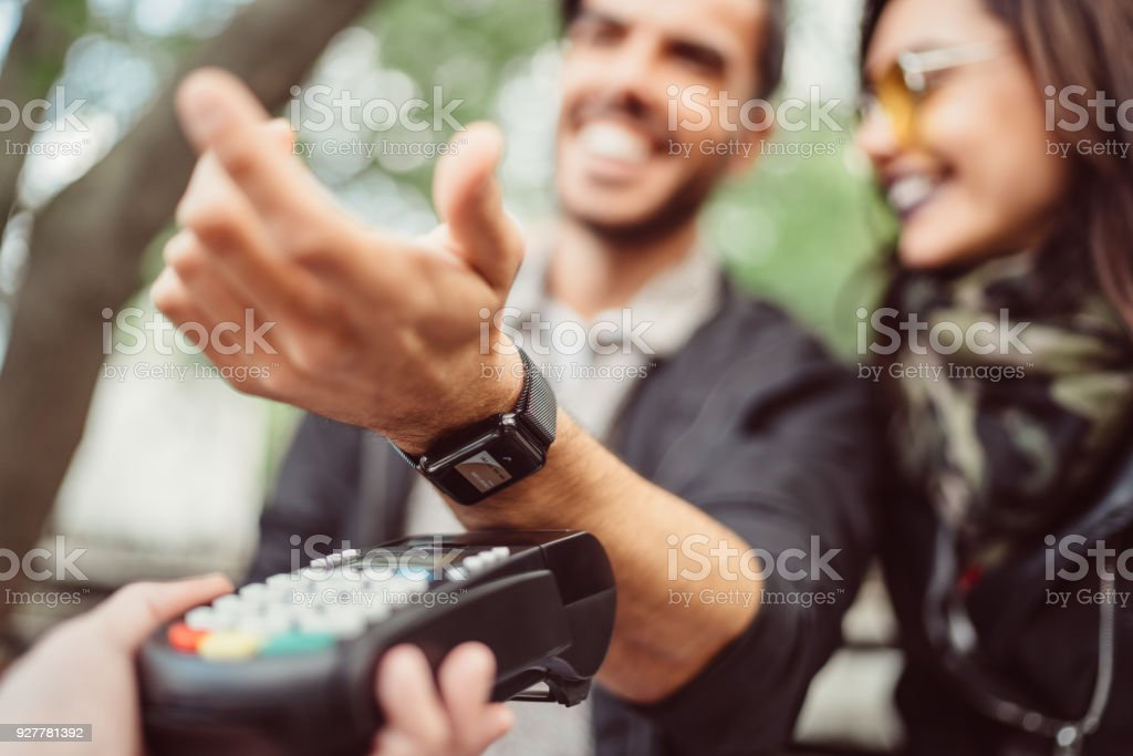 Man paying contactless with smartwatch stock photo