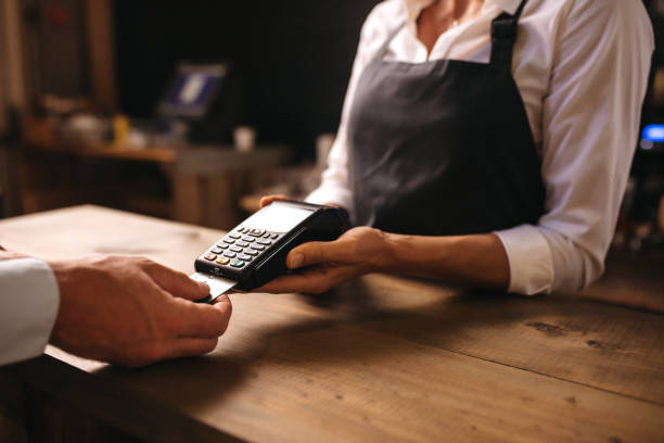 Man paying for coffee by credit card at coffee shop stock photo