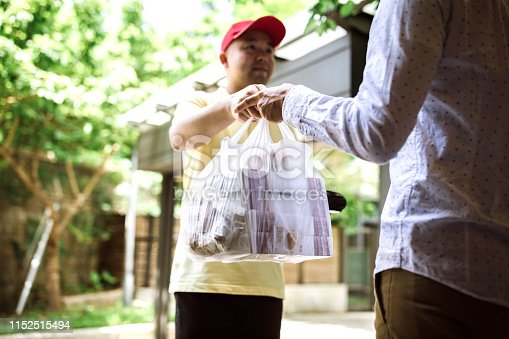 Man Paying For Takeout Food to Delivery Person Using Credit Card Reader