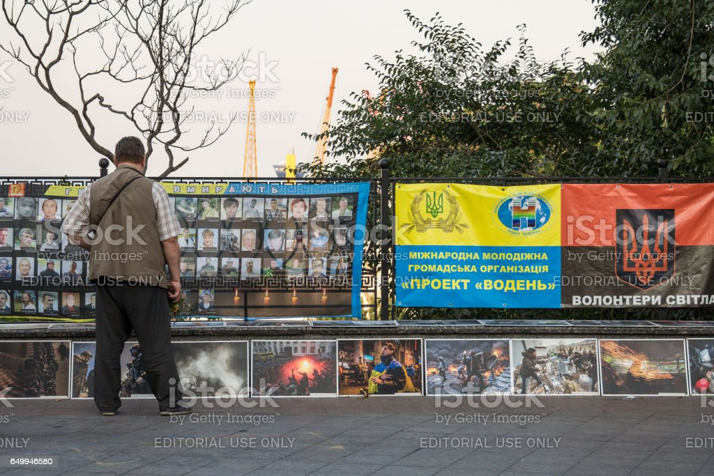 Odessa, Ukraine - August 14, 2015: Man paying respect to the people killed during the Maidan - Euromaidan revolts of 2014 at a memorial erected in Odessa stock photo