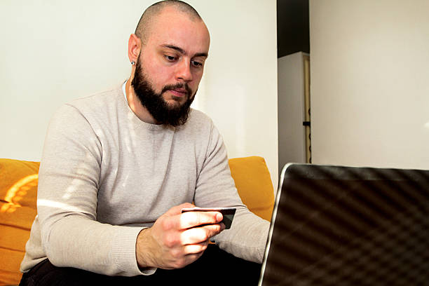 Man paying the bills by credit card using laptop - foto de acervo