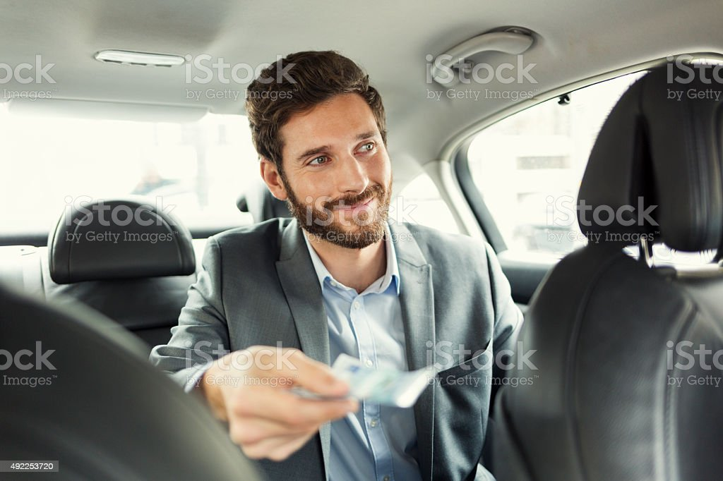 Man paying the taxi with the cash stock photo