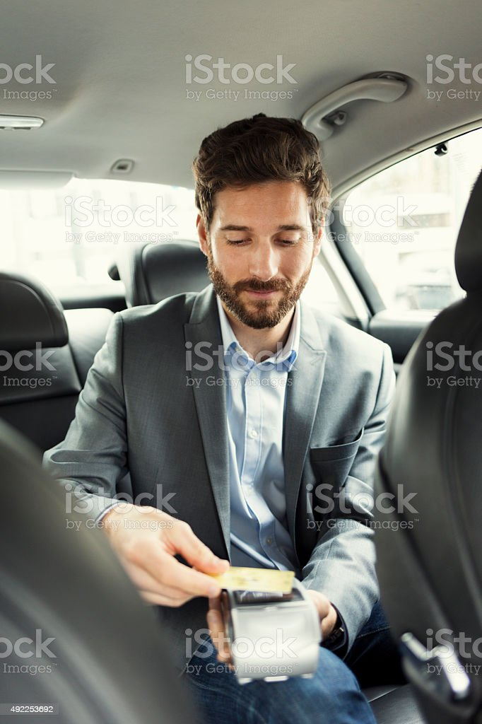 Man paying the taxi with the credit card. NFC technology stock photo
