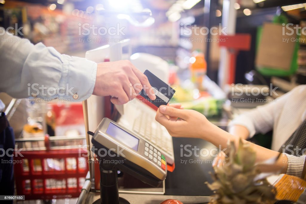 Homem de pagamento com cartão de crédito no supermercado - foto de acervo