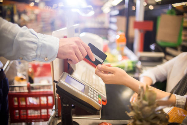 Man Paying with Credit Card in Supermarket Side view close up of unrecognizable customer handing credit card to cashier paying via bank terminal at grocery store checkout stock pictures, royalty-free photos & images