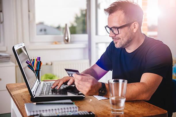 man paying with credit card on laptop - brille bestellen stock-fotos und bilder