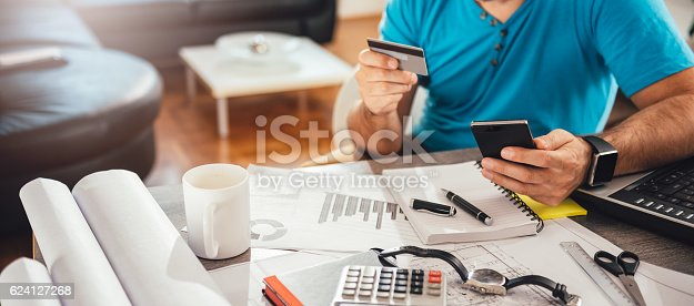 istock Man paying with credit card on smart phone 624127268