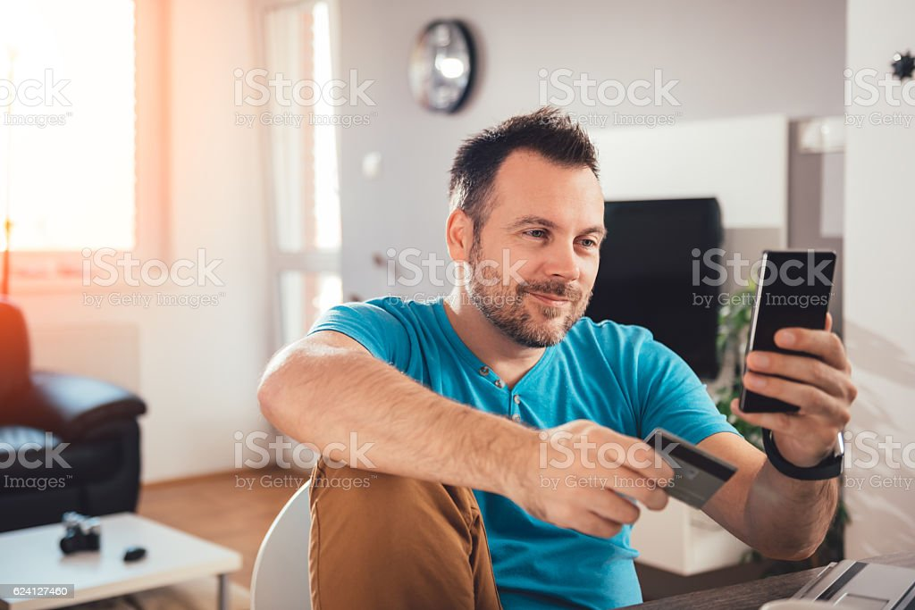 Man paying with credit card on smart phone - Royalty-free Adult Stock Photo