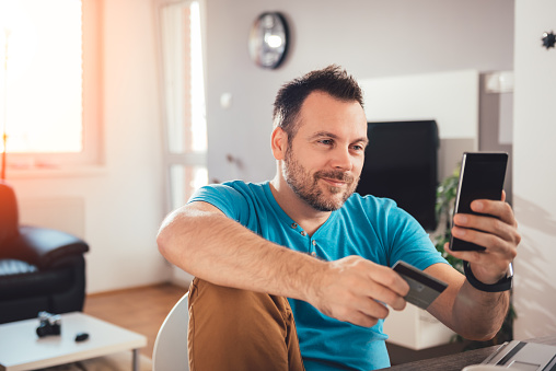 Man Paying With Credit Card On Smart Phone Stock Photo - Download Image Now