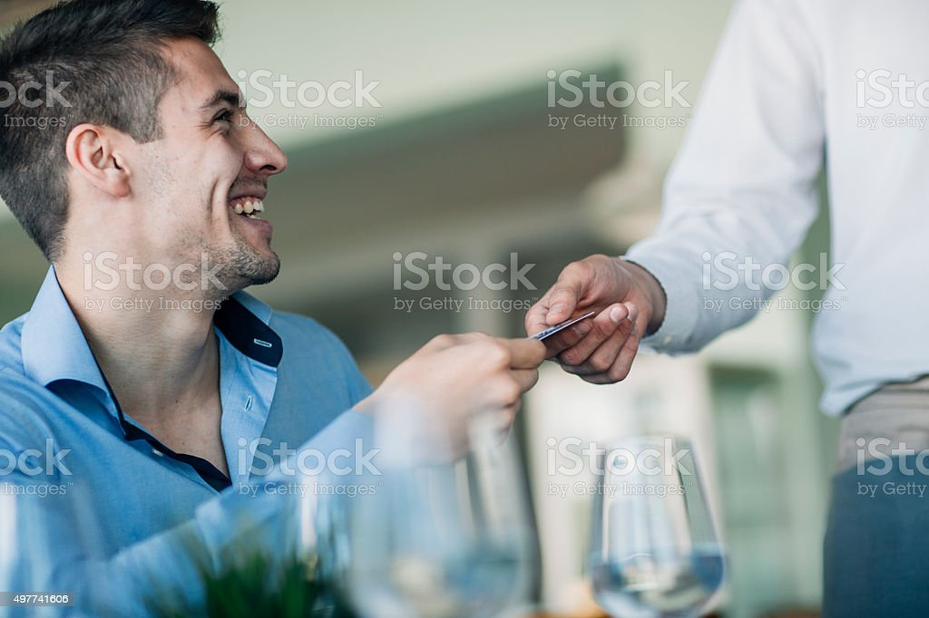 Man Paying With His Credit Card In Restaurant. stock photo