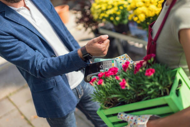 Man paying with his smart watch at the garden center stock photo