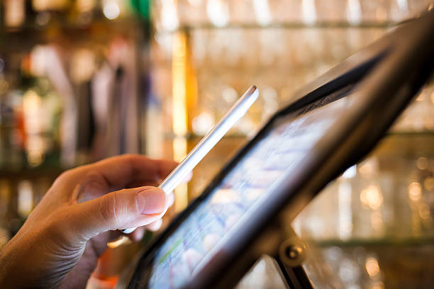 Man paying with NFC technology on mobile phone, in restaurant Male Close-up electronic payment hand cell phone bar cafe radio frequency identification stock pictures, royalty-free photos & images
