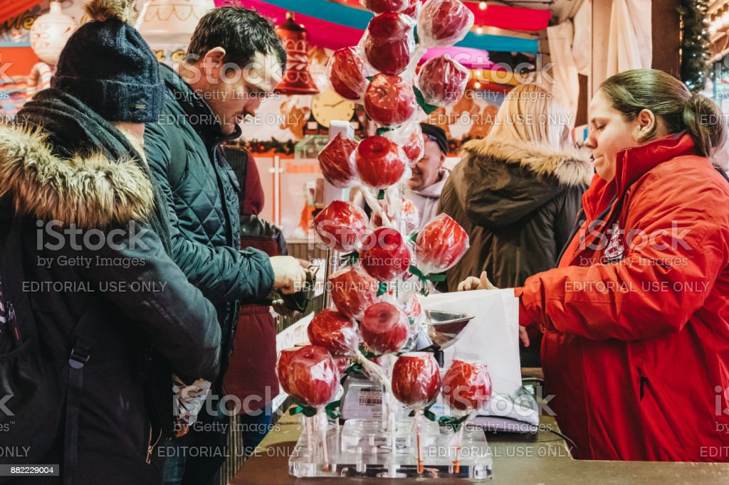Man pays for sweets at a stall in Winter Wonderland Christmas Fair in London, UK stock photo