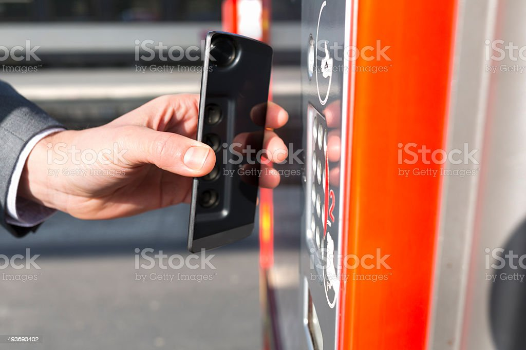 Man pays transport ticket with mobile phone on platform stock photo