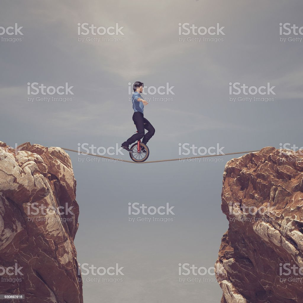 Man pedaling on rope between two mountains - stock photo