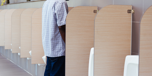 man peeing in male toilet urinals