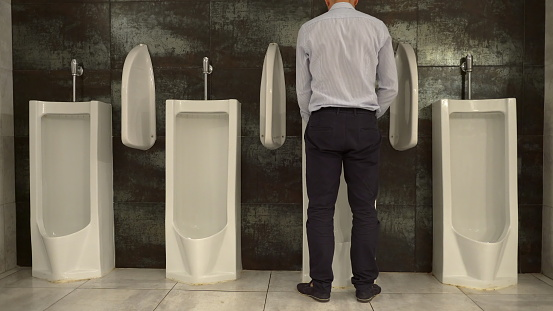 Man Peeing to Urinal in the Restroom