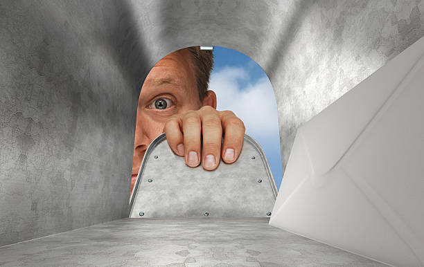 Man peeking into a mailbox and seeing that he has mail stock photo