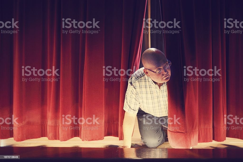 Man Peeking Through Red Stage Curtains royalty-free stock photo