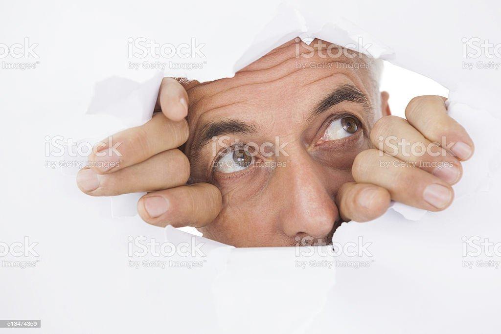 Man peeking through torn white surface stock photo