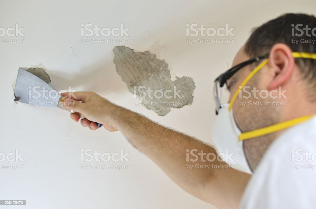 Man Peeling a Ceiling stock photo