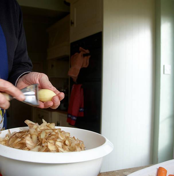 mann peeling kartoffeln in der küche - peeling zu hause machen stock-fotos und bilder