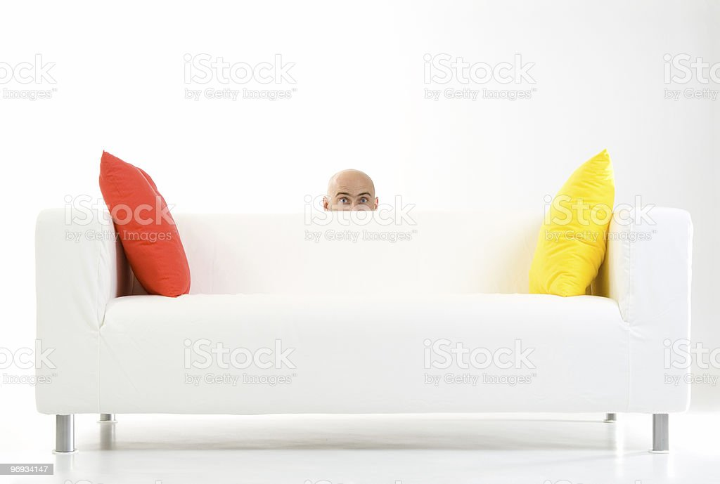Man peeping from behind sofa royalty-free stock photo