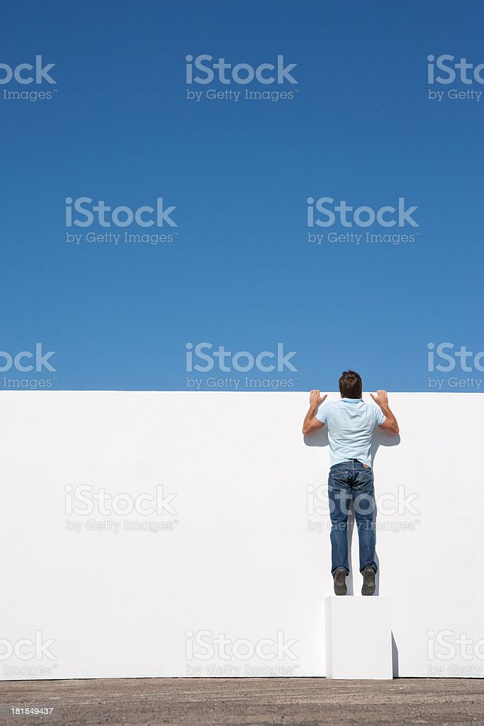 Man peering over wall outdoors with blue sky stock photo