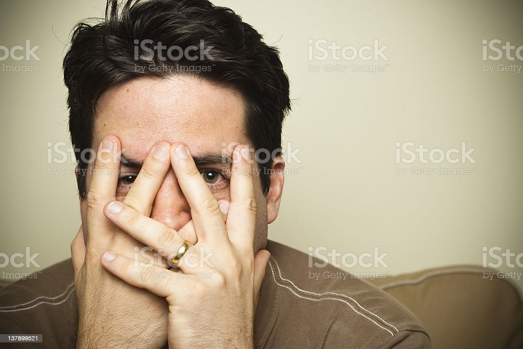 Man peers through his fingers royalty-free stock photo