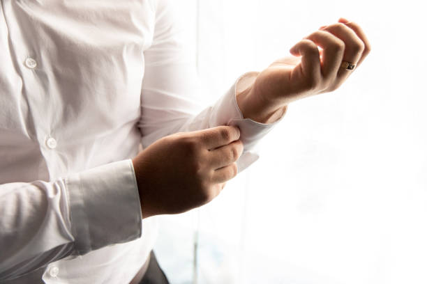 Man. People, business,fashion and clothing concept - close up of man dressing up and adjusting white shirt with cufflinks stock photo