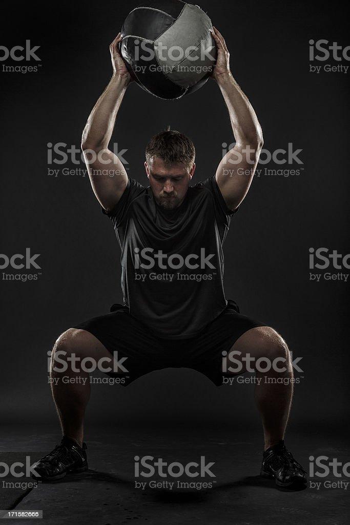 A man performing a medicine ball squat stock photo
